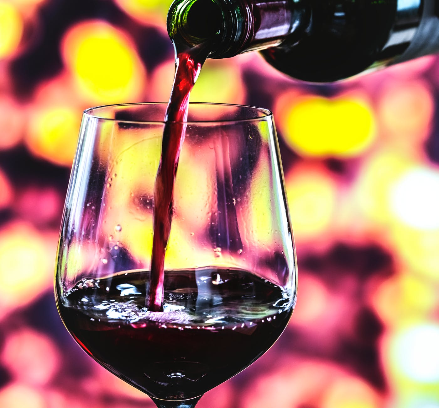 selective focus photography of wine bottle pouring on wine glass